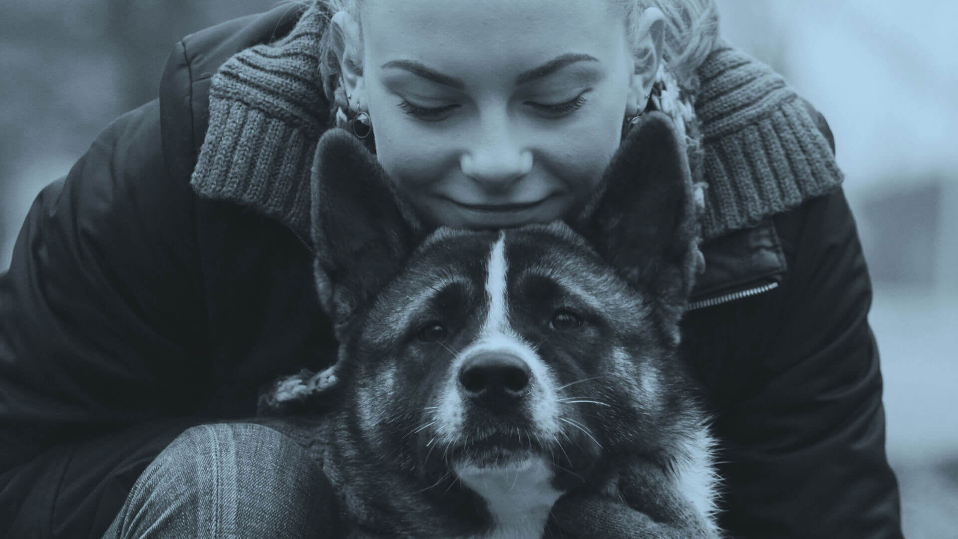 Happy female dog owner lovingly looking at her dog