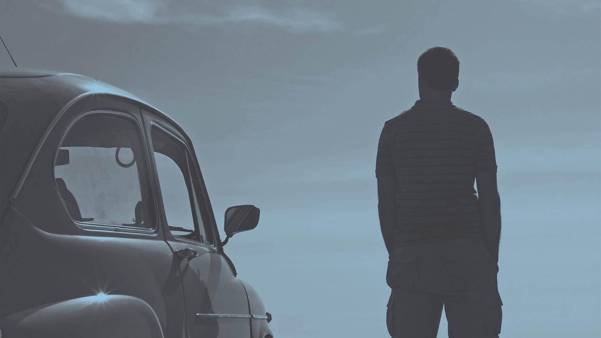 Man standing in front of car remembering his deceased loved one